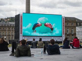 Zuschauer liegen auf dem Schlossplatz beim Internationalen Trickfilm Festival. Foto:
