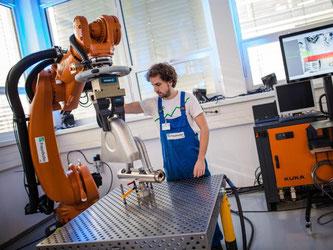 """""""Future Work Lab"""" des Fraunhofer Instituts in Stuttgart: Ein Roboterarm transportiert schwere Produktionsgegenstände, um Mitarbeiter zu entlasten. Foto: Christoph Schmidt"""