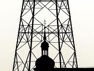Ein Kirchturm isthinter einem Strommast zu sehen. Foto: Karl-Josef Hildenbrand/Archiv