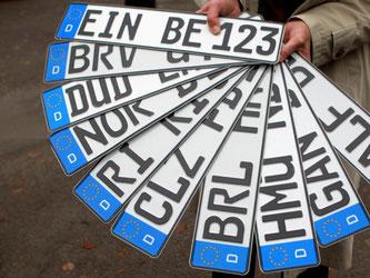 Ein Mann zeigt KFZ Kennzeichen mit alten Buchstabenkombinationen. Foto: Hubert Jelinek/Archiv