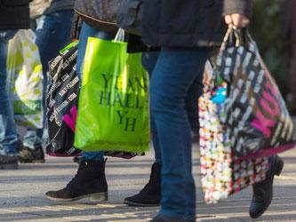 Menschen tragen ihre gefüllten Einkaufstüten durch die Straßen. Foto: Nikolai Huland/Archiv