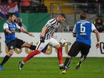 Frankfurts Torschütze Danny Blum (M) führt den Ball gegen Tom Schütz (r) und Fabian Klos. Foto: Andreas Arnold
