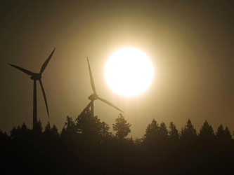 Die Sonne geht hinter Windrädern auf. Foto: Patrick Seeger/Archiv