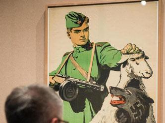 Ein Besucher betrachtet ein sowjetisches Plakat aus dem Jahr 1945 mit der Aufschrift «Der Feind ist listig - sei auf der Hut!». Foto: Gregor Fischer