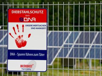 Ein Schild am Solarpark in Senftenberg (Brandenburg) weist auf den Diebstahlschutz der Solarmodule durch eine künstliche Hightech-DNA hin. Foto: Patrick Pleul