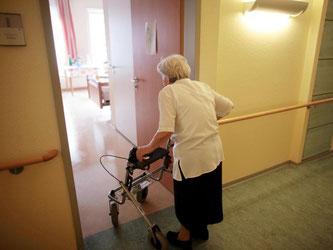 Eine Frau geht mit ihrem Rollator in ihr Zimmer. Foto: Oliver Berg dpa/Archiv