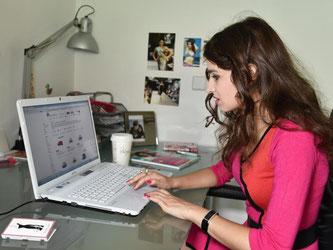 Eine junge Frau schaut sich online Schuhe an. Foto: Jens Kalaene