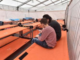 Zwei Flüchtlinge sitzen auf einem Notbett. Foto: Uli Deck/Archiv