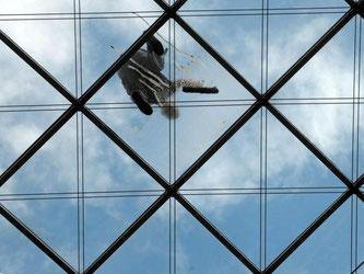 Ein Fensterputzer auf dem gläsernen Dach eines Geschäftshauses. Foto: Matthias Hiekel