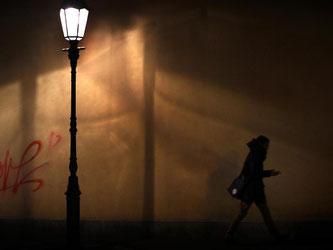 Eine Frau geht im Licht einer Straßenlaterne spazieren. Foto: Karl-Josef Hildenbrand