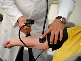 Ein Hausarzt mißt einer Patientin den Blutdruck. Foto: Bernd Weißbrod/Archiv