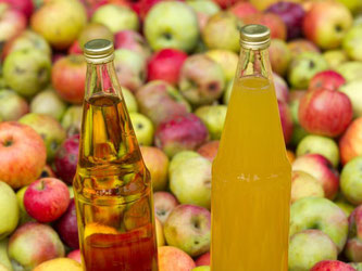 Zwei Flaschen mit Apfelsaft stehen in einem Behälter mit Äpfeln. Foto: Patrick Pleul/Archiv
