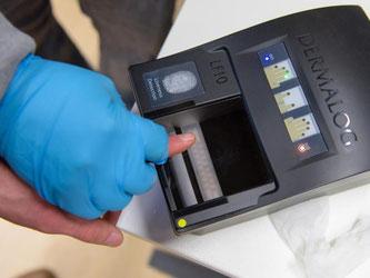 Ein Mitarbeiter nimmt einen Fingerabdruck. Foto: Oliver Dietze/Archiv