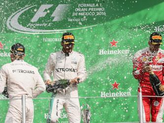 Lewis Hamilton (M), Nico Rosberg (l) und Sebastian Vettel bei der Siegerehrung in Mexiko-Stadt. Foto: José Mendez