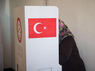 Eine Frau mit Kopftuch steht in einem Wahllokal in einer Wahlkabine. Foto: Lino Mirgeler/Archiv