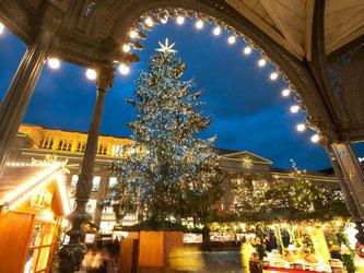 Ein Weihnachtsbaum strahlt auf einem Weihnachtsmarkt. Foto: Nikolai Huland/Archiv
