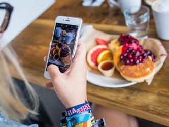 So schmeckt es manchen noch besser: Eine junge Frau fotografiert mit einem Smartphone ihr Essen. Foto: Sophia Kembowski