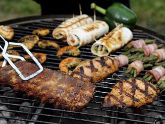 Spareribs, Gemüse, gefüllte Hühnerbrust und Garnelen liegen auf dem Grill. Foto: Daniel Maurer