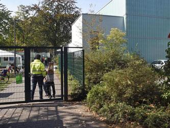 Ein Mitarbeiter eines Sicherheitsdienstes bewacht in Köln Porz den Zugang zu der als Flüchtlingsunterkunft genutzten Turnhalle. Foto: Henning Kaiser