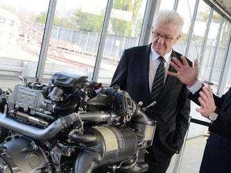 Winfried Kretschmann betrachtet einen Dieselmotor. Foto: Franziska Kraufmann/Archiv