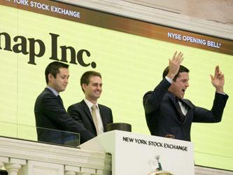 Die beiden Unternehmensgründer Evan Spiegel (M) und Bobby Murphy (l) läuten im März die Eröffnungsglocke der New Yorker Börse, während Börsenchef Thomas Farley (r) jubelt. Foto: Richard Drew
