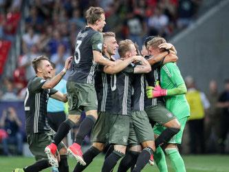 Die deutschen Spieler bejubeln ihren Torwart Julian Pollersbeck (r) nach dem Sieg über England im Elfmeterschießen. Foto: Jan Woitas