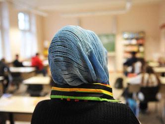 Eine Schülerin mit Kopftuch nimmt am Unterricht in einer Schule teil. Foto: Bernd Thissen/Illustration