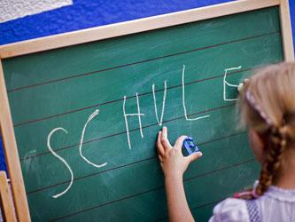 Ein Kind schreibt das Wort «Schule» an eine Tafel. Foto: Arno Burgi/Archiv