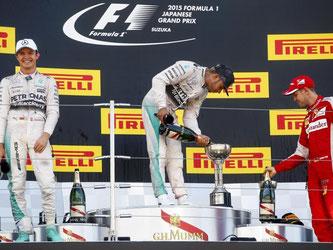 Lewis Hamilton feiert vor den beiden deutschen Piloten Nico Rosberg und Sebastian Vettel den Sieg. Foto: Diego Azubel