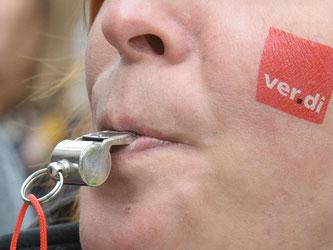 Eine Frau pfeift auf einer Trillerpfeife während einer Kundgebung. Foto: Franziska Kraufmann/Archiv