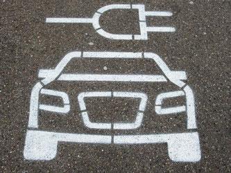 Ein Auto mit Elektrostecker ist auf einem Parkplatz aufgemalt. Foto: Armin Weigel/Archiv