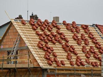 Ziegel liegen auf dem Dach eines Rohbaus. Die Bausparkassen setzen ihren harten Kurs fort. Foto: Daniel Karmann
