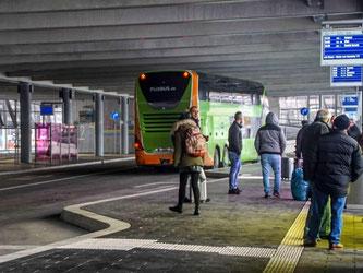 Reisende stehen am Fernbus-Bahnhof am Flughafen in Stuttgart. Foto: Frank Dettenmeyer