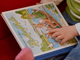 Ein Kind liest in Stuttgart im Buch «Ferien in der Häschenschule». Foto: Franziska Kraufmann