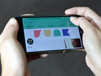 """Eine Frau schaut sich auf ihrem Smartphone die App """"funk"""" an. Foto: Maurizio Gambarini"""