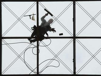 Zwei Gebäudereiniger putzen in Dresden das gewölbte Glasdach des World Trade Centers. Foto: Sebastian Kahnert/Illustration