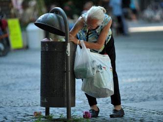 Eine ältere Frau sucht in Mülleimern nach Pfandflaschen. Foto: Martin Schutt/Archiv