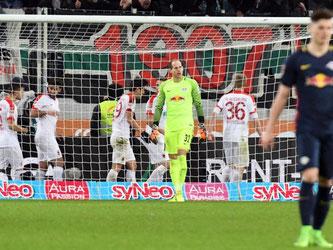 Augsburgs Spieler jubeln nach dem 2:2-Ausgleich hinter dem Tor von Leipzigs Torwart Peter Gulacsi. Foto: Stefan Puchner