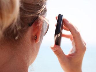 Urlaubsgrüße per Telefon durchgeben, kann teuer werden. Deshalb sollten sich Verbraucher über spezielle Tarife für Auslandstelefonie und Roaming informieren. Foto: Friso Gentsch