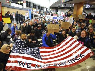 """Demonstranten sitzen im Flughafen von Seattle auf dem Boden und halten ein Plakat mit der Aufschrift """"Wir sind Amerika"""". Foto: Genna Martin"""
