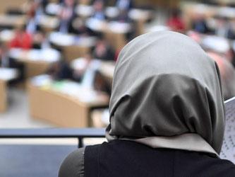 Eine Schülerin mit Kopftuch verfolgt eine Landtagsdebatte. Foto: Marijan Murat/Archiv