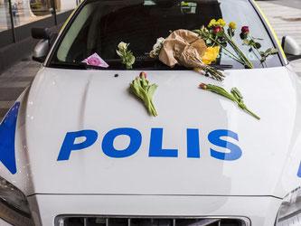 Blumen auf der Motorhaube eines Polizeifahrzeugs in Stockholm. Foto: Kenta Jönsson