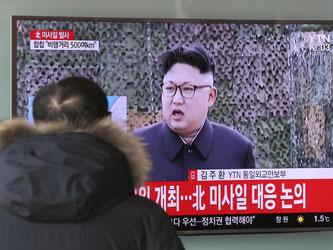 """An einem Bahnhof in Seoul ist auf einem Fernseher der nordkoreanische Machthaber Kim Jong Un zu sehen. Das Schriftband auf dem TV lautet: """"Der Norden hat eine Rakete abgefeuert"""". Foto: Lee Jin-Man"""