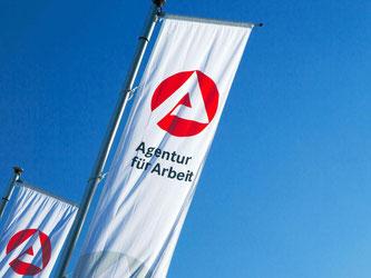 Fahnen wehen vor einem Gebäude der Agentur für Arbeit. Foto: Jens Büttner/Archiv