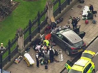 Das Standbild aus einem Video zeigt Hilfskräfte, die in der Nähe des britischen Parlaments neben einem Auto einen Verletzten behandeln. Foto: ITN via APTN/AP