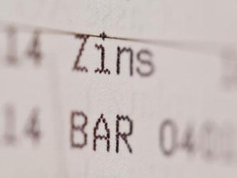 Die Einträge «Zins» und «Bar» sind in einem Sparbuch zu sehen. Foto: Daniel Karmann/Archiv