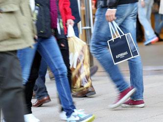 Passanten gehen mit Einkaufstüten durch eine Innenstadt. Foto: Bodo Marks/Archiv