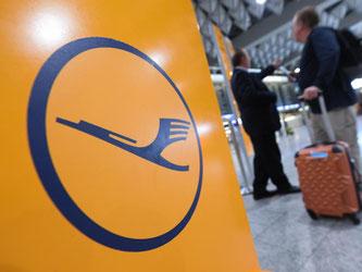 Ein Mann mit Gepäck neben einem Lufthansa-Logo. Foto: Arne Dedert
