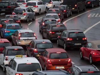 Autos warten in Stuttgart an einer Ampelanlage. Foto: Marijan Murat/Archiv