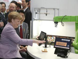 Bundeskanzlerin Angela Merkel und Japans Premierminister Shinzo Abe während ihres Rundgangs über die CeBIT Messe in Hannover. Foto: Friso Gentsch